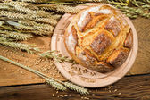 Freshly baked country bread on old wooden table — Stock Photo