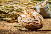 Freshly baked loaf of bread and a bag with grains — Stock Photo