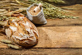 Loaf of bread and a bag with grains — Stock Photo