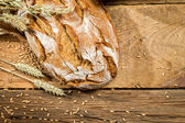 Freshly baked loaf of bread on old wooden table — Stock Photo