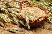 Full grain basket on old wooden table — Stock Photo
