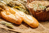 Two baguettes and a basket of grain — Stock Photo