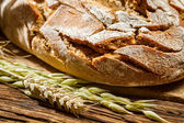 Closeup of wholemeal bread on old wooden table — Stock Photo
