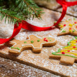 Gingerbread cookies for Christmas with red ribbon on a wooden ta — Stockfoto