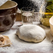 Closeup of sprinkling flour pizza dough — Stock Photo