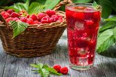 Juice of fresh raspberries served with ice in a glass — Stock Photo