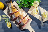 Ingredients and the fresh fish before frying on blue table — Stock Photo