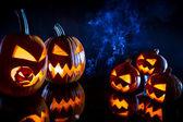Kleine en grote pompoenen voor halloween met kaarsen op een zwarte b — Stockfoto