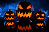 Three halloween pumpkins and blue smoke — Stock Photo