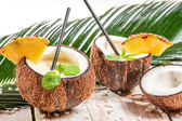 Pinacolada in a coconut on old white table — Stock Photo