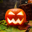Glowing halloween pumpkin on leaves — Stock Photo