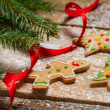 Gingerbread cookies for Christmas with red ribbon on a wooden ta — Stock Photo