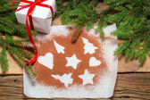 Shapes of gingerbread cookies on a sheet of paper with gift — Stock Photo