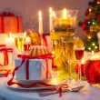 Candlelight and gifts all around the Christmas table — Stok fotoğraf