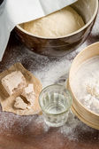 Yeast dough let stand to rise on ld wooden table — Stock Photo