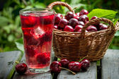 Freshly harvested sweet cherries and juice — Stock Photo