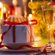 Candlelight and gifts all around Christmas table — стоковое фото #37011457