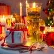 Candlelight and gifts all around the Christmas table — Stockfoto