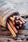 Cinnamon sticks in a burlap sack on the wooden table — Stock Photo