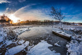 Sunrise on winter lake covered with snow — Stock Photo