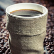 Freshly hot coffee in burlap sack — Stock Photo