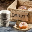 Hot coffee and box full of donuts — Stock Photo