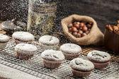 Falling icing sugar on fresh chocolate muffins — Stock Photo