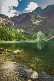 Mountain lake in summer on the background of rocky mountains — Stock Photo