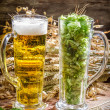 Ears of wheat in gold surrounded by fresh beer hops — Stock Photo