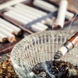 Closeup of fuming cigarette in old pipe — Stock Photo #39525949
