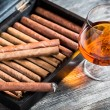 Stock Photo: Cigars in humidor and cognac