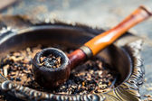 Closeup of old wooden pipe in an ashtray — Stock Photo
