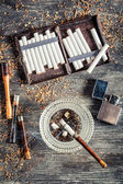 Cigarettes, ashtray and a smoking pipe — Stock Photo