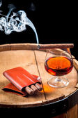 Glass of cognac and cigar on old barrel — Stock Photo