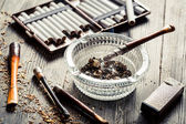 Thin pipe with burning cigarette — Stock Photo