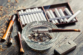 Glass ashtray with thin wooden pipes, cigarettes and lighter aro — Stock Photo