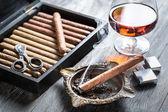 Burning cigar in ashtray and cognac — Stock Photo