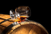 Glass of cognac on the old wooden barrel — Stock Photo