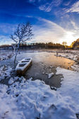 Old boat on the lake covered with snow in winter — Stock fotografie