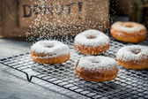Falling powder sugar on donuts — Stock Photo