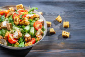 Healthy Caesar salad made of fresh vegetables on blue table — Stock Photo