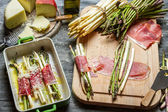 Asparagus wrapped in Parma ham with cheese — Stock Photo