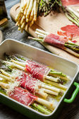 Preparation of asparagus wrapped in Parma ham with cheese — Stock Photo