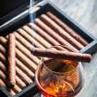 Burning cigar on humidor and cognac in glass — Stock Photo #41418939