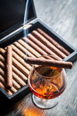 Burning cigar on humidor and cognac in glass — Foto de Stock