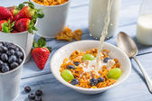 Cornflakes with fruits flooded with milk — Stock Photo