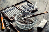 Glass ashtray with thin wooden pipes, cigarettes and lighter aro — Stok fotoğraf