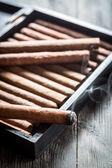 Smoke rising from a burning cigar on wooden humidor — Stock Photo