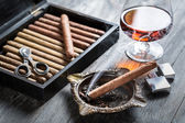 Burning cigar in ashtray and cognac — Stok fotoğraf