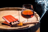 Cognac in a glass on barrel and burning cigar — Stock Photo